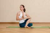 Caucasian woman is practicing yoga at studio (ardhamatsyendra)