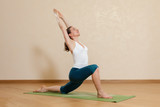 Caucasian woman is practicing yoga at studio (anjaneyasana)