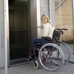 Frau in Rollstuhl fährt in Fahrstuhl