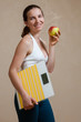 Caucasian woman posing with scales and apple