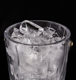 Ice and ice bucket over black background