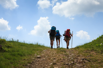 Group of hikers in the Carpathian mountains in front of blue sky