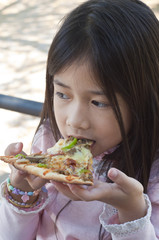 Little Asian girl enjoy eating pizza.