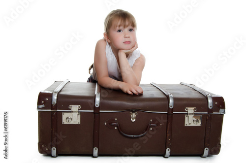 The little girl on old suitcases