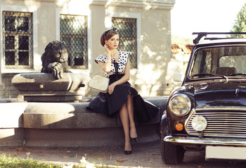 A sexy woman sitting next to a retro car on the street