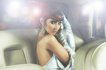 A beautiful celebrity woman sitting in a luxury car