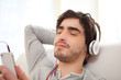 Young relaxed man listenning music in the sofa