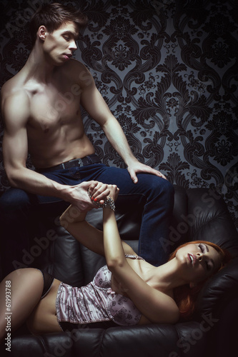 A young and sexy couple in erotic lingerie on a black sofa