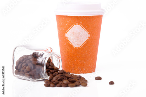 An orange takeout cup and coffee beans in a jar