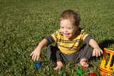 Laughing Down Syndrome child in grass with toys