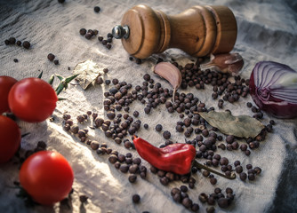 Allspice pepper on tablecloth and a grinder