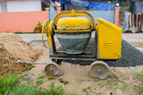 Cement mixer with sand and gravel mixing trough at a building si