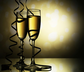 Glasses of champagne with serpentine on light background