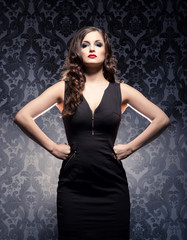 An emotional woman in a fashion dress on a glamour background