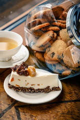A jar of cookies and tea  with a cheesecake