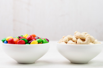 Cashew nuts and candies in bowls side by side
