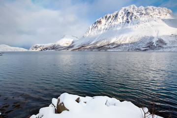 Norwegian fjord surrounded by snow mountains