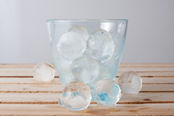 Water glass full of ice balls on a wood