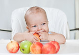 happy baby boy eating apples
