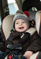 happy little boy in car seat