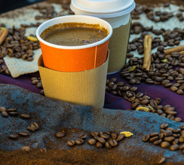 Coffee beans and ground coffee around papercups