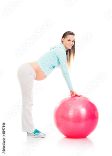 A young pregnant woman working out with a fitness ball