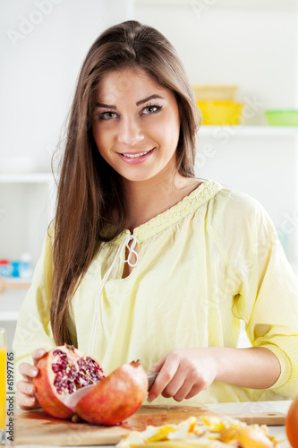 Beautiful young woman cutting pomegranate