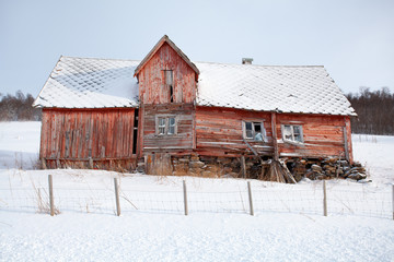 Abandoned wooden house in the snow