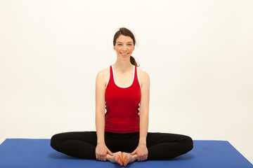 Die junge Frau macht Pilates Übungen auf einer Matte
