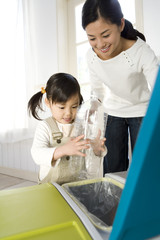 mother and girl separating plastic bottles