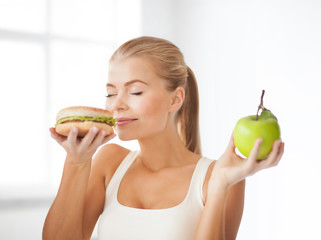 smiling woman smelling hamburger and holding apple