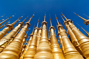 Golden stupas of Shwe Indein Pagoda over blue sky. Myanmar