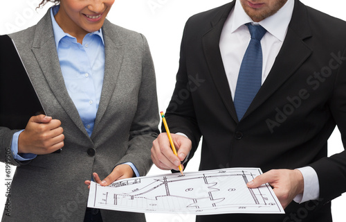 businesspeople with clipboard, blueprint, helmet