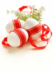 festive eggs decorated with red ribbon - symbol of Easter