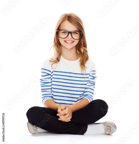 smiling girl in eyeglasses sitting on floor