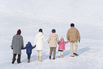 three-generation family walking on snow