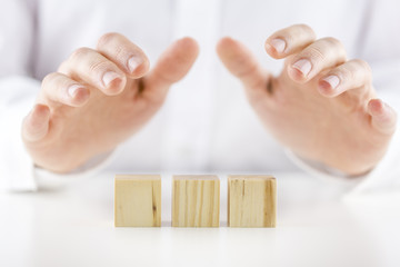 Man holding protective hands above three wooden cubes