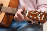 Closeup shot of men playing on classic wooden guitar