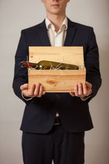 Portrait of elegant man in suit holding wooden box with wine