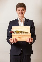 elegant man smiling and carrying wooden box with red wine