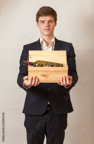 Handsome elegant man in black suit holding wooden box with wine