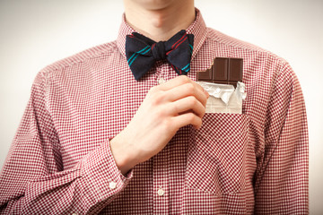 man in shirt and bow tie taking chocolate out of breast-pocket
