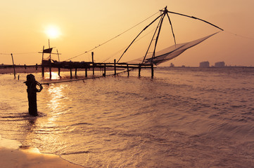 Sunset at tropical beach with chinese fishing nets. India
