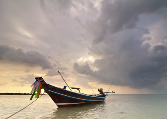 Sunset at tropical beach with Thai fishing boat. Thailand