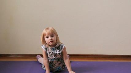 маленькая девочка играет, дурачится, делает упражнения
