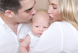 Young parents kissing baby
