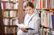 Young pregnant woman reading book in library