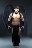 Handsome muscular guy posing as fallen angel