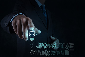 businessman hand pointing  light bulb with design word KNOWLEDGE