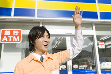 salesclerk of convenience store raising hand